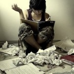 Girl sitting amidst lots of scrunched up paper